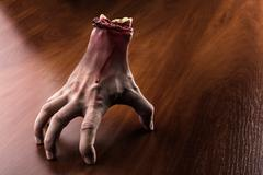 Bloody arm stands on the table - stock illustration