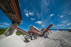 excavator digs against the sky in summer - stock photo