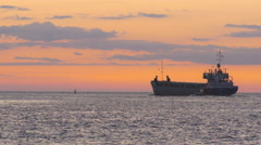 Stock Video Footage of Maritime pilot convoys a bulk carrier leaving port into sea during vivid sunset