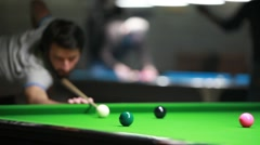 A concentrated snooker player trying to hit the ball precisely as he can Stock Footage