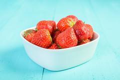 Strawberry Bowl On Blue Wood Background - stock photo