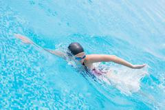 Woman in goggles swimming front crawl style - stock photo