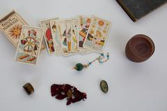 tarot cards with old book and candle - stock photo