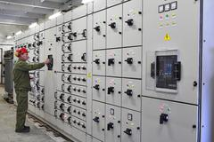 Engineer electrician switches switchgear equipment. Stock Photos