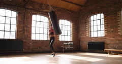 Kickboxing woman training punching bag in fitness studio - stock footage