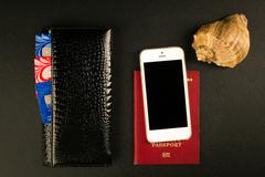 Passport, wallet and smartphone - travel concept, black background - stock photo