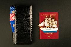 Passport, wallet and sailfish- travel concept, black background - stock photo