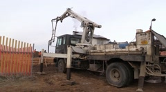 Concrete pump truck at countryside land plot entry - stock footage