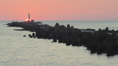 Sun setting behind a breakwater with a lighthouse at the tip Stock Footage