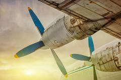 plane flying into the sunset - stock photo