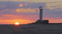 Vivid time lapse of sun setting behind a breakwater with a lighthouse Stock Footage