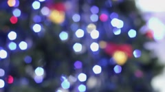 Closeup of toy with bells near illuminated christmas tree out of focus Stock Footage