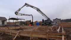Builders flood concrete foundation with concrete pump truck into the formwork Stock Footage