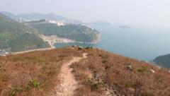 POV walk trodden path at island mountain top, panoramic view Stock Footage