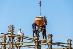 Worker working in construction on blue sky - stock photo