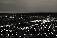 Abstract white black circular bokeh background, city lights in the twilight w Stock Photos