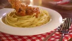 Pouring sauce onto spaghetti - stock footage