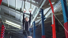 4K Professional male gymnast training on the rings at the gym.  Stock Footage