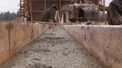 Builder aligns the horizontal level of the concrete with a trowel in formwork Stock Footage