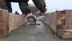 Builder aligns the horizontal level of the concrete with a trowel in foundation Stock Footage