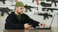 A man working at a laptop in gun shop, holding a gun in his hand Stock Footage