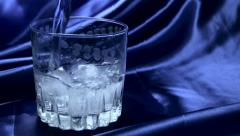 Water pouring into a glass with ice slow motion - stock footage