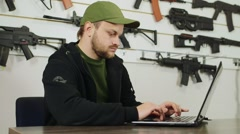 An arms dealer at work, working with a laptop Stock Footage