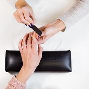 Image of hands polishing index finger - stock photo