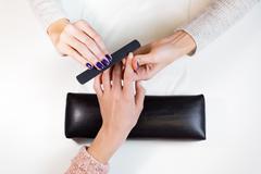 Manicurist polishing index finger for manicure - stock photo