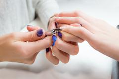 Finger nail care by manicure specialist in salon - stock photo