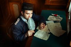 Man is thinking when he wrote the manuscript. - stock photo