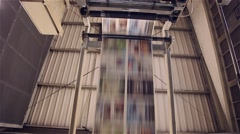 Newspaper in a print line being printed on a printing press Stock Footage