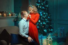 Stock Photo of Woman strokes flirting nose man in the Christmas night.