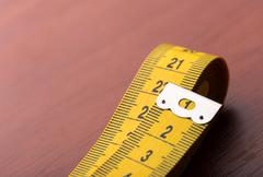Yellow measurement tape - stock photo