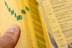 Hand searching the yellow pages Stock Photos