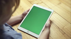A young girl holding a tablet with a green screen - stock footage