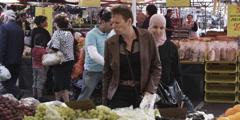 Slow motion women tasting grapes market Stock Footage