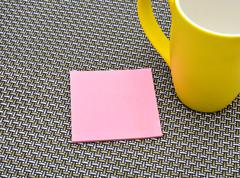 Notepad with yellow cup on pattern background Stock Photos