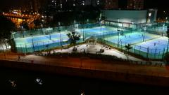 Tennis courts illuminated in night, general pan view, dark city outside Stock Footage