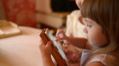Little girl plays a game on the phone at the table in a restaurant Stock Footage