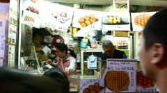 Waffles kiosk on night street, POV walk around, several citizens wait in queue Stock Footage