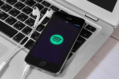 IPhone 5s on laptop with mobile application for Spotify on the screen Stock Photos