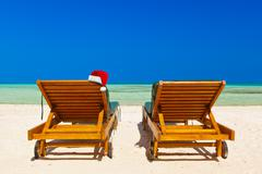 Chairs on tropical beach and Santa Claus red christmas hat Kuvituskuvat