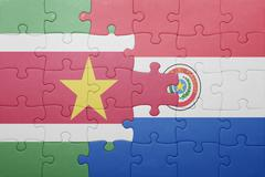puzzle with the national flag of paraguay and suriname - stock photo