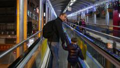 Man and his little son run up on escalator, follow camera, night time Stock Footage