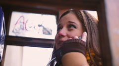 Woman talking on the phone in telephone booth Stock Footage