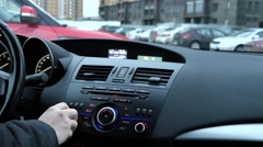 A man adjusts a radio receiver and adjusts the volume in the car - stock footage