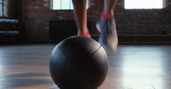 Fitness woman doing toe taps training with medicine ball at gym Stock Footage