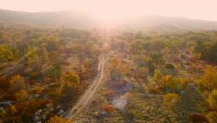 Stock Video Footage of 4K Aerial: Dirt road in Wasteland, Sunset, Autumn