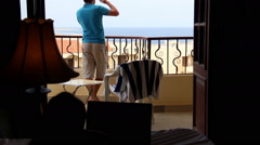 man leaves a balcony overlooking the sea and kissing a girl on the bed - stock footage